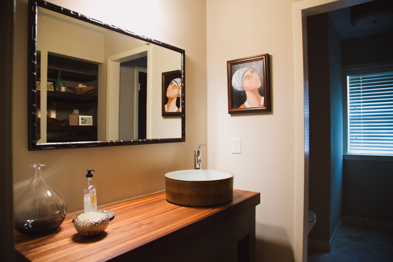 The half bath off the main living area features a beautiful, custom made sink and cabinet that was later copied by a designer.