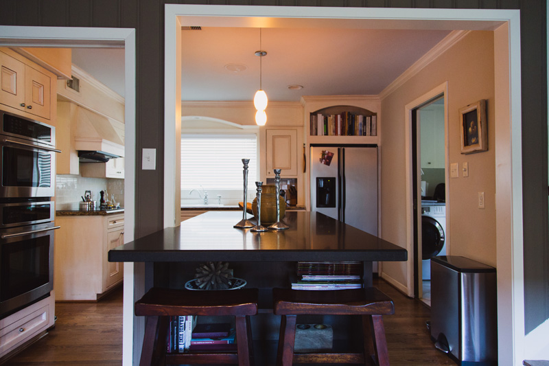 A honed granite island and counter bridges the kitchen and living areas.