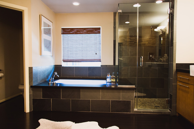 The shower has two rainfall shower heads; the tub has slate siding and a honed granite top.
